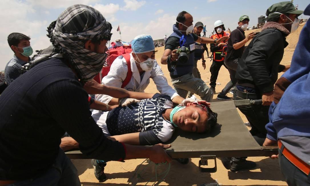 Ferido nas manifestações em Gaza é colocado em maca: um adolescente de 14 anos foi morto durante os confrontos Said Khatib / AFP
