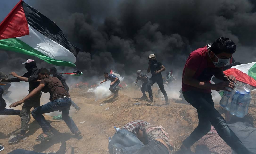 Participantes do protesto em Gaza procuram de proteger da resposta do Exército de Israel Ibraheem Abu Mustafa / REUTERS