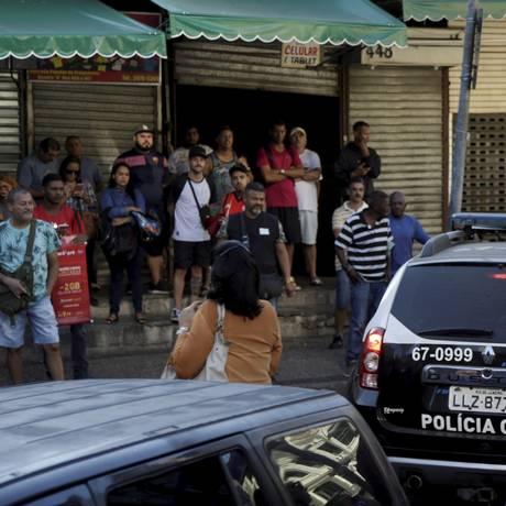 Grupo observa a movimentação de policiais no camelódromo da Uruguaiana Foto: Gabriel de Paiva / Agência O Globo