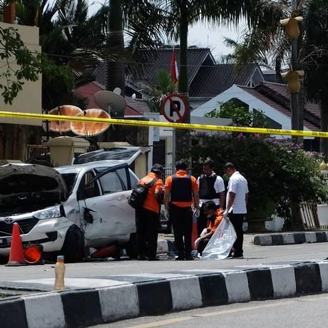 Policiais examinam o veículo usado no ataque a delegacia Foto: DEDY SUTISNA / AFP
