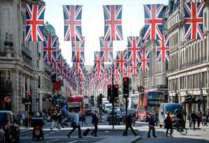 Bandeiras. O símbolo nacional enfeita a Regent Street, em Londres, às vésperas do casamento real Foto: TOLGA AKMEN / AFP