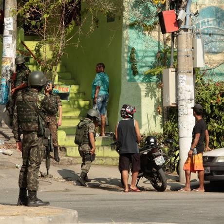 Militares do Exército revistam moradores no acesso ao Morro do Preventório Foto: Brenno Carvalho / Agência O Globo