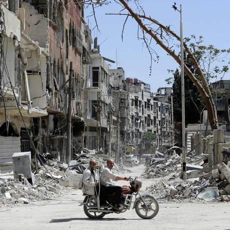 Cidadãos sírios passam em frente a destroços na em Ghouta Oriental, subúrbio de Damasco Foto: LOUAI BESHARA / AFP