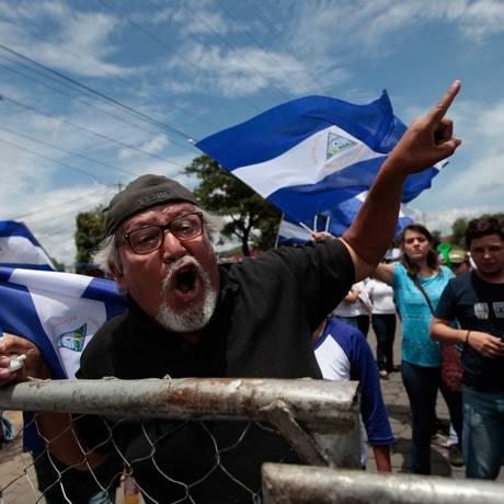 Manifestantes gritam em protesto contra presidente da Nicarágua na frente do local onde acontece diálogo entre governo e opositores Foto: DIANA ULLOA / AFP