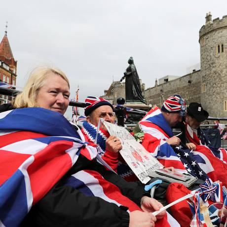 Novos tempos. Fãs da família real guardam lugar junto ao Castelo de Windsor, no trajeto da carruagem que levará Harry e Meghan: realeza se transformou em marca global Foto: MARKO DJURICA/REUTERS