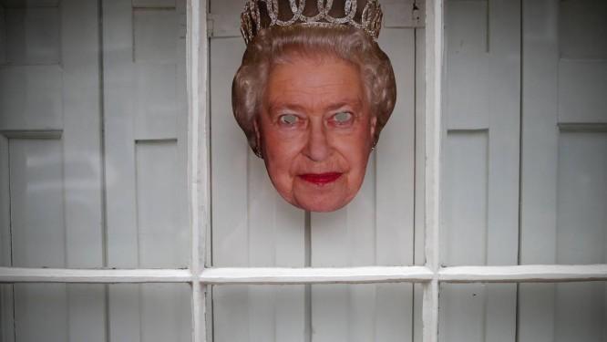 Máscara da Rainha Elizabeth II decora janela em Windsor, no Reino Unido Foto: DAMIR SAGOLJ / REUTERS