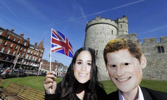 Pessoas com máscaras do príncipe Harry e de Meghan Markle em frente ao Castelo de Windsor, onde se realizará no casamento real de 19 de maio Foto: Kirsty Wigglesworth / AP