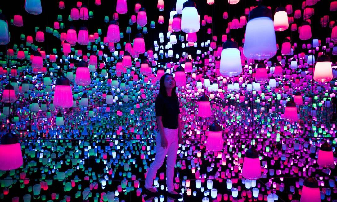 """Sala de instalação digital com lâmpadas penduradas que se iluminam e, à medida que o visitante se aproxima, as luzes """"se movem"""" de uma lâmpada para outra Foto: BEHROUZ MEHRI / AFP"""