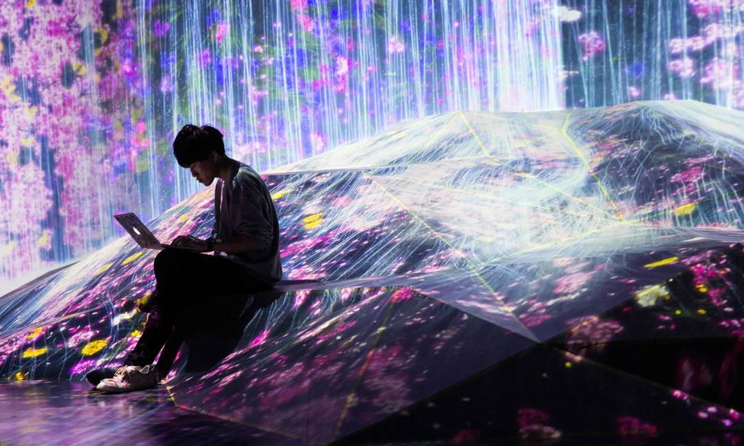"""Membro do coletivo Teamlab trabalha em seu laptop em uma instalação digital repleta de flores que parecem fluir por uma colina, no Mori Building Digital Art Museum, em Tóquio. A """"cachoeira"""" que escorre pela parede de um quarto e atravessa o andar é uma ilusão digital criada pelo grupo, conhecido internacionalmente por sua inovadora """"arte digital"""", que combina projeções, sons e espaços cuidadosamente projetados para criar experiências imersivas de outro mundo Foto: BEHROUZ MEHRI / AFP"""