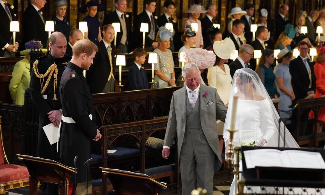 Príncipe Harry, olha para sua noiva, Meghan Markle, enquanto ela chega acompanhada do Príncipe Charles, na Capela de São Jorge, durante a cerimônia de casamento Foto: JONATHAN BRADY / AFP