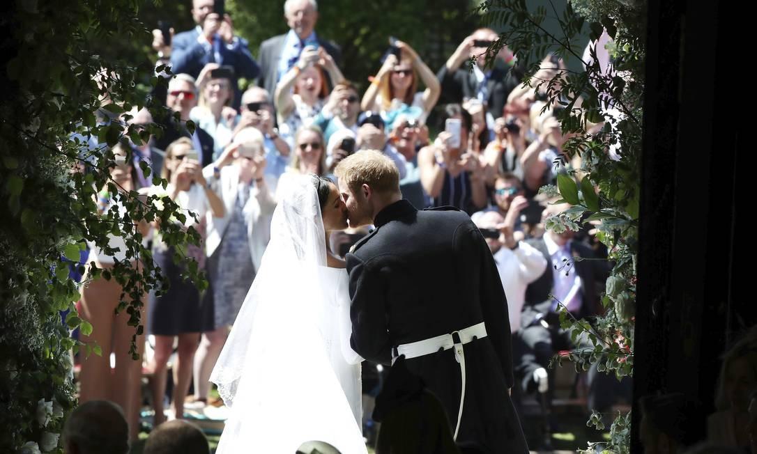 Príncipe Harry e Meghan Markle se beijam nos degraus da Capela de São Jorge após a cerimônia de casamento em Windsor) Foto: Danny Lawson / AP