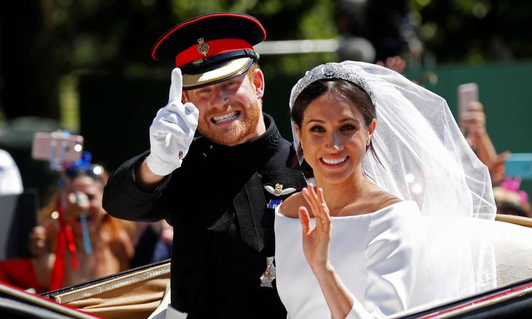 O príncipe Harry e sua esposa Meghan acenam enquanto cavalgam em uma carruagem puxada por cavalos após a cerimônia de casamento na capela de St. Georges no Castelo de Windsor em Windsor, Inglaterra. Foto: DAMIR SAGOLJ / REUTERS