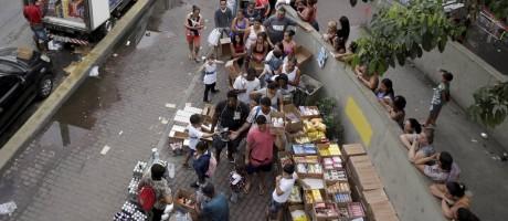 Caminhão Rei do 1 real junto à Lagoa-Barra e a um carro da PM: clientes fazem fila para acessar calçada onde mercadorias são expostas em caixas de papelão Foto: Marcelo Theobald