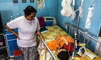 Uma mulher aguarda ao lado do filho em uma sala de neurocirurgia do hospital infantil JM de los Rios, em Caracas. A crise na Venezuela fez a mortalidade infantil aumentar 30,12% de acordo com os dados oficiais Foto: FEDERICO PARRA / AFP