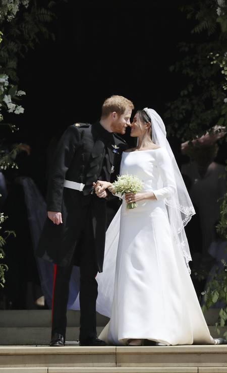 O príncipe Harry e a atriz americana Meghan Markle trocaram alianças neste sábado. o vestido da noiva foi assinado pela grife francesa Givenchy, pilotada pela estilista britânca Clare Waight Keller Foto: Jane Barlow / AP