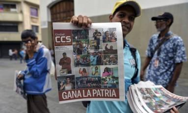 Jornaleiro segura uma edição mostrando o resultado da eleição venezuelana: vitória de Maduro não é reconhecida por vários países Foto: LUIS ROBAYO / AFP