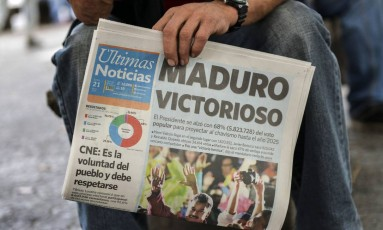 Venezuelano leva jornal que anuncia a vitória de Maduro nas eleições presidenciais de domingo Foto: LUIS ROBAYO / AFP