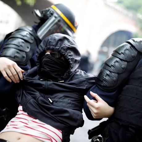 Conflito nas ruas: manifestantes mascarados são presos pela polícia francesa em onda de protestos por funcionalismo público Foto: CHRISTIAN HARTMANN / REUTERS