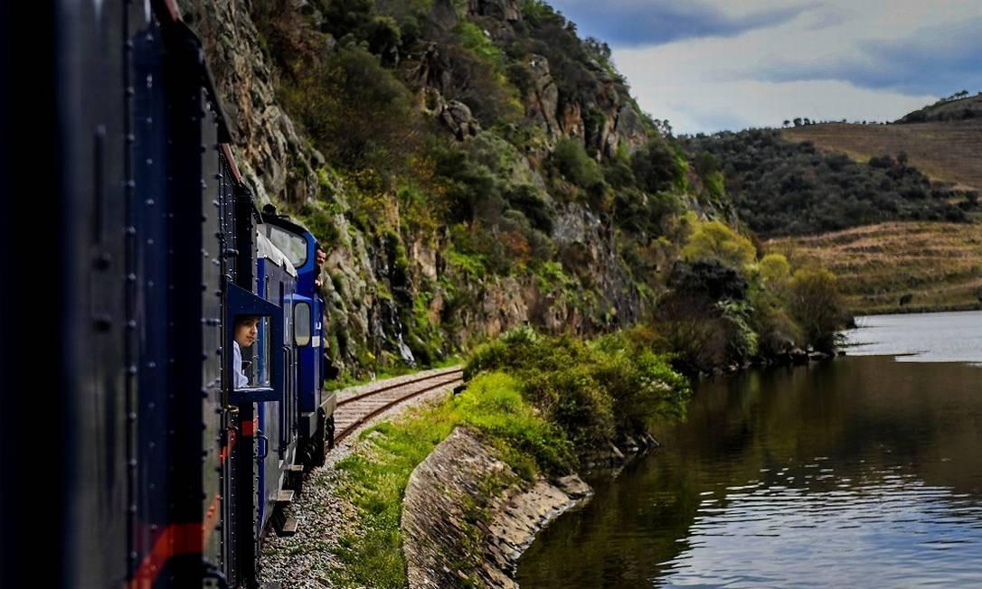 Passageiro observa a paisagem do Vale do Douro a bordo do trem, que foi inaugurado em 1890 e foi o meio de transporte oficial de reis e presidentes portugueses Foto: Patrícia de Melo Moreira / AFP