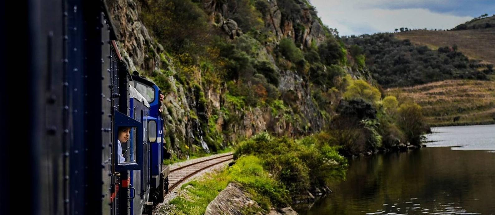 Passageiro observa a paisagem do Vale do Douro a bordo do Presidential Train, composição de luxo que faz viagens gastronômicas no norte de Portugal Foto: Patrícia de Melo Moreira / AFP