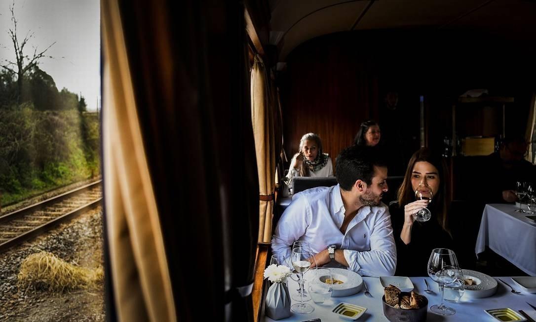 """Casal come no vagão-restaurante o menu preparado pelo chef estrelado Rui Paula, um dos convidados para a atual temporada de primavera da viagem gastronômica """"The Presidential"""" Foto: PATRICIA DE MELO MOREIRA / AFP"""