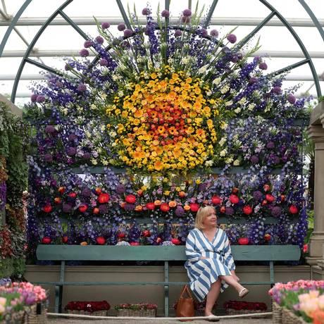 Um visitante se senta e aprecia uma exposição de flores durante o evento Foto: DANIEL LEAL-OLIVAS / AFP