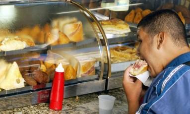 Homem consome lanche em barraca de comida na Central do Brasil, no Rio: muitas pessoas obesas também sofrem com depressão Foto: Márcia Foletto/09-02-2004