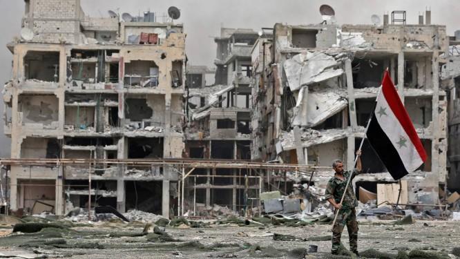 Um soldado sírio levanta a bandeira do país diante dos edifícios destruídos do antigo campo de refugiados palestinos de Yarmouk, perto de Damasco; à medida que o regime aumenta seu controle territorial, cresce a tensão com os Estados Unidos Foto: LOUAI BESHARA / AFP