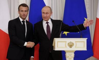 Em São Petesburgo, presidente da França, Emmanuel Macron, aperta a mão de presidente russo, Vladimir Putin Foto: Dmitri Lovetsky / AP