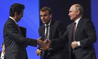Novos amigos. Putin (à direita) cumprimenta Abe, junto a Macron, em São Petersburgo Foto: KIRILL KUDRYAVTSEV / AFP