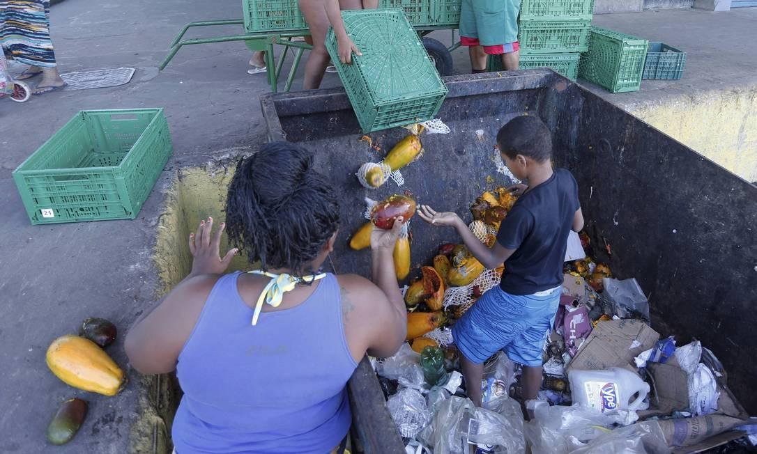 Sempre atentas para encontrarem verduras e frutas aproveitáveis, famílias inteiras circulam pelo interior do Ceasa e buscam os alimentos em caçambas de lixo Foto: Domingos Peixoto / Agência O Globo