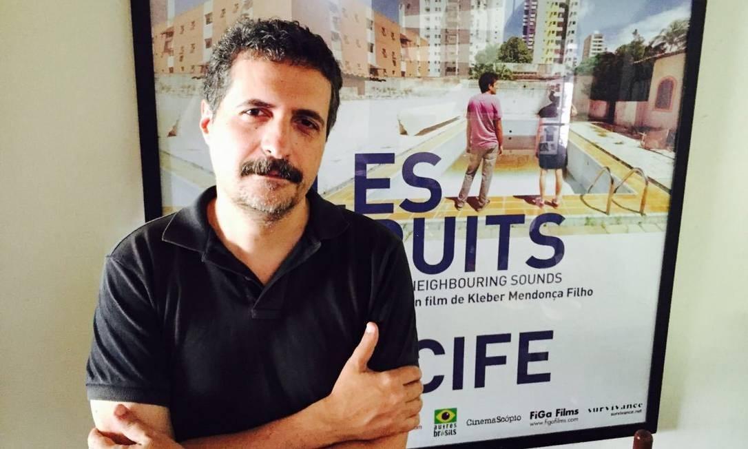 Kleber Mendonça Filho diante de cartaz internacional de 'O som ao redor' Foto: Divulgação