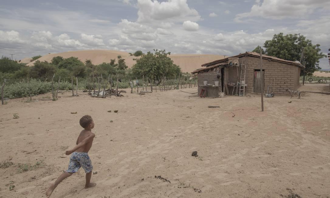 Na margem esquerda do Rio São Francisco, a duna da Geleia (ao fundo) pouco a pouco engole o povoado de Mucambo: a casa do pescador João Pereira Matos, de 74 anos, e de sua família tem os dias contados Foto: / Daniel Marenco