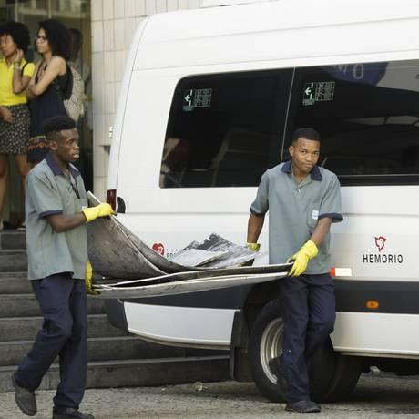 Funcionários retiram pedaços de placas danificadas pelo incêndio Foto: Gabriel de Paiva / Agência O Globo