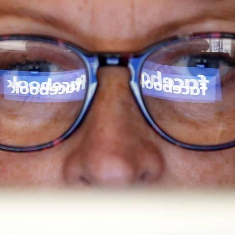 Logomarca do Facebook aparece refletida no óculos de mulher. Foto: Regis Duvignau/Reuters