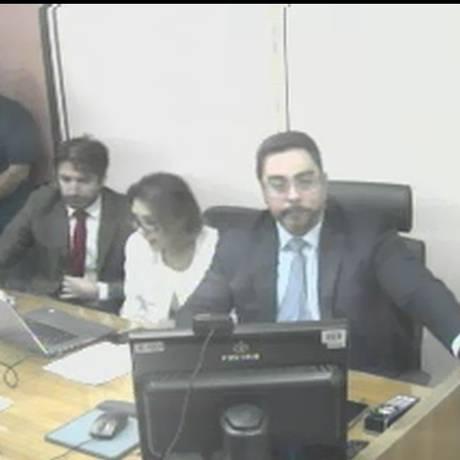 Bretas olha para a TV onde aparece a imagem de Lula durante o depoimento Foto: Reprodução