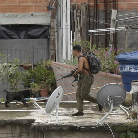 Traficante flagrado armado com fuzil corre sobre telhados durante operação do Bope no Morro da Babilônia Foto: Marcelo Carnaval / Agência O Globo