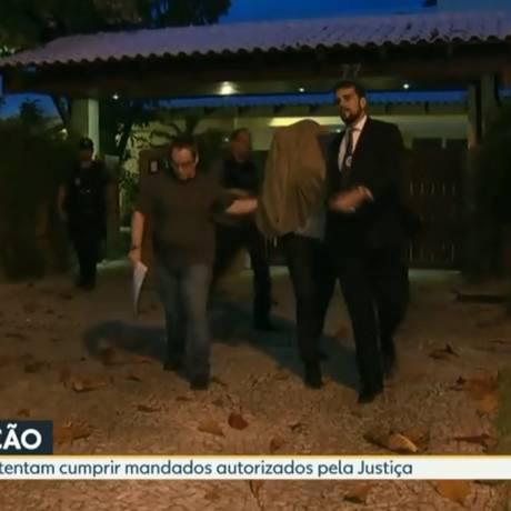 Eduardo Cruz deixa sua casa, com o rosto coberto por um casaco Foto: TV Globo / Reprodução
