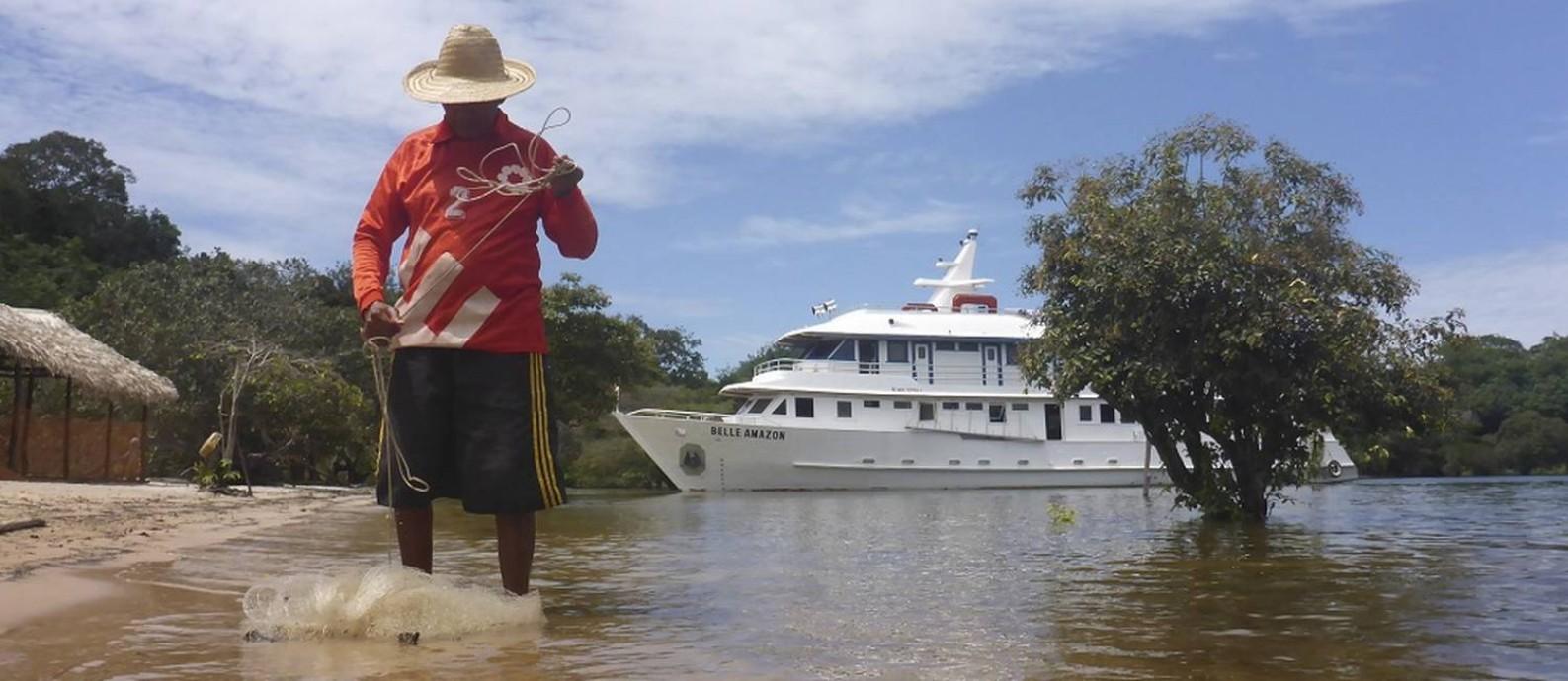 Pescador com o barco Belle Amazon ao fundo Foto: Gabriel de Paiva