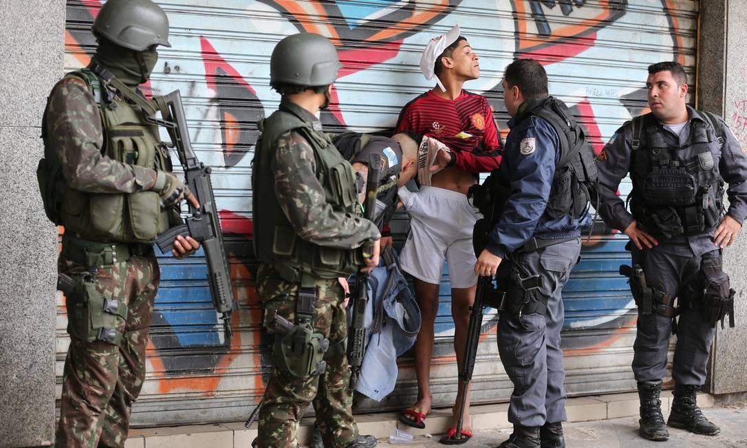Morador da Rocinha é revistado por policiais militares Foto: Marcia Foletto / Agência O Globo