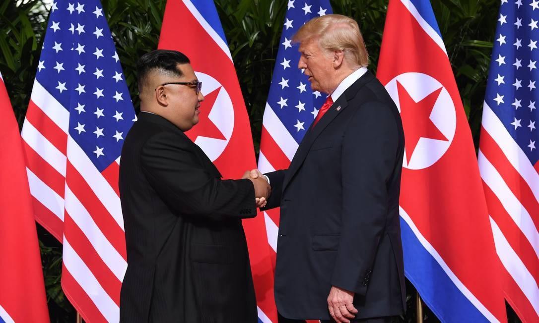 No primeiro encontro entre um presidente americano e um líder norte-coreano, Donald Trump aperta a mão de Kim Jong-un no luxuoso Hotel Capella, em Cingapura. Na agenda, a desnuclearização da Coreia do Norte SAUL LOEB / AFP