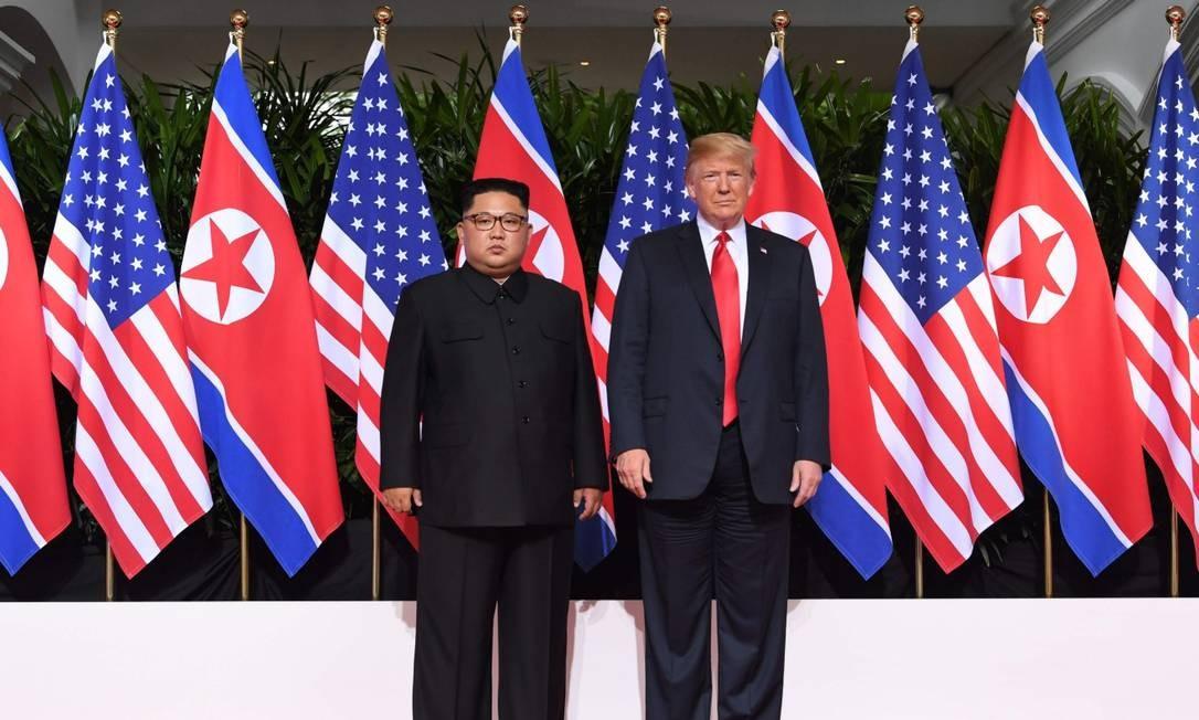 Líder supremo norte-coreano, Kim Jong-un, e presidente americano, Donald Trump, posam lado a lado para multidão de fotógrafos que acompanhavam o encontro histórico em Cingapura SAUL LOEB / AFP