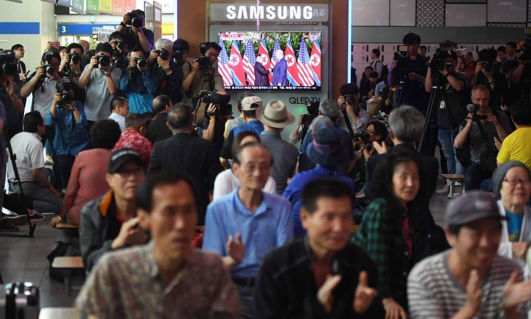 Em Seul, na Coreia do Sul, pessoas assistem ao vivo ao encontro histórico entre Kim e Trump; tensão nuclear na Península Coreana afeta vida da população Foto: JUNG YEON-JE / AFP