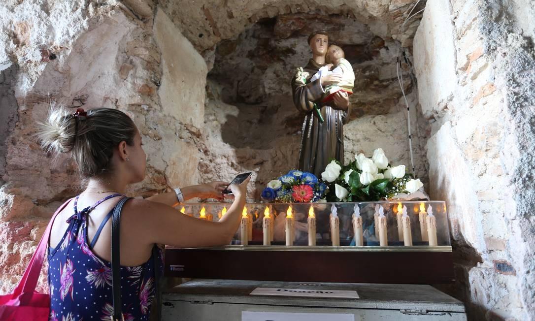 Fiel tira fotos das vela em frente à imagem de Santo Antônio Foto: Fabiano Rocha / Agência O Globo