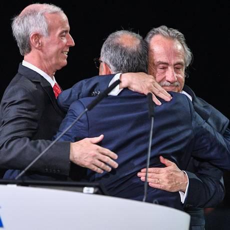 Os presidentes das federações dos EUA (Carlos Cordeiro), México (Décio de Maria Serrano) e Canadá (Steve Reed) comemoram vitória da candidatura conjunta Foto: MLADEN ANTONOV / AFP