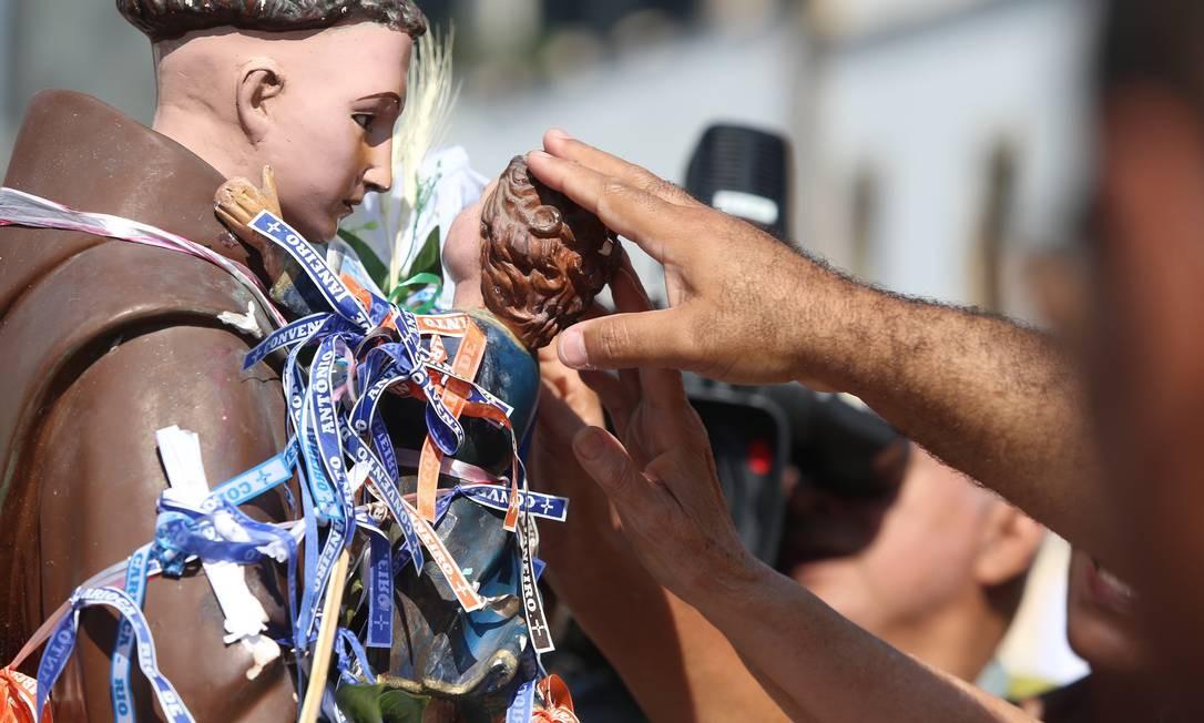 Devoto toca a imagem de Santo Antônio com o Menino Jesus para pedir bênçãos Foto: Fabiano Rocha / Agência O Globo