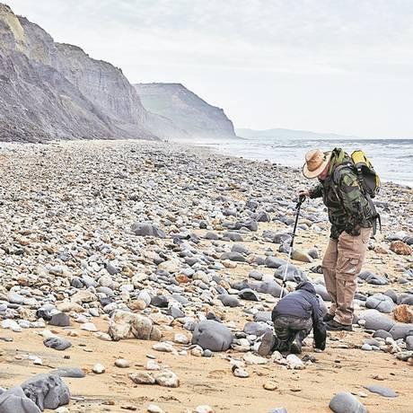 Guia mostra a uma criança como coletar fósseis em Dorset Foto: Andy Haslam/The New York Times