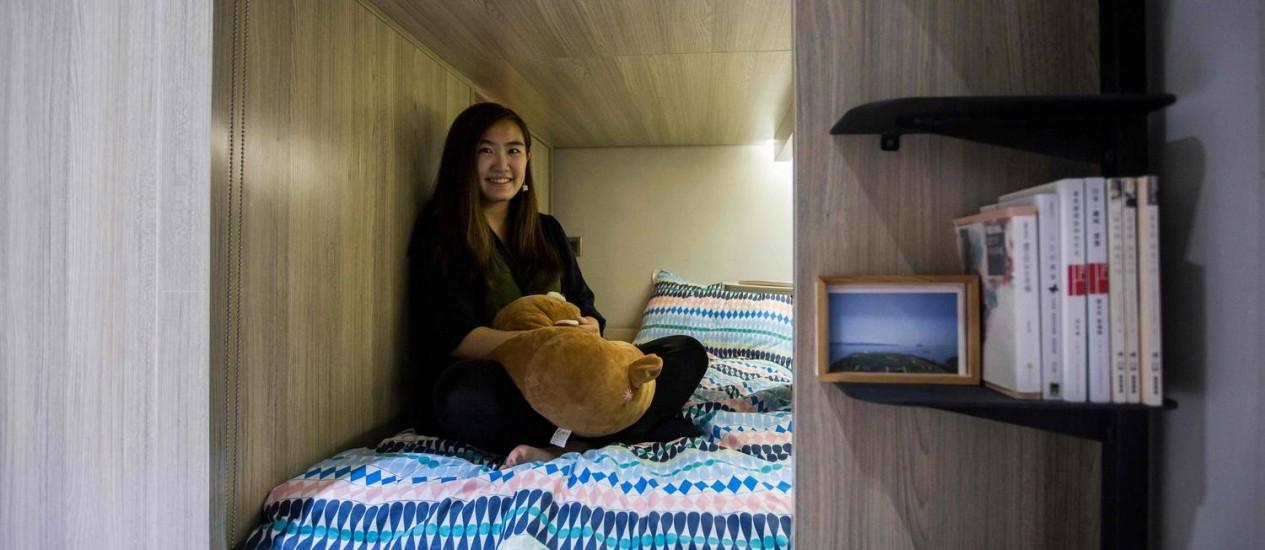 Michelle Chau em sua cama, no espaço que aluga num prédio de áreas compartilhadas no distrito de Mong Kok, em Hong Kong: nanoapartamentos Foto: ISAAC LAWRENCE / AFP