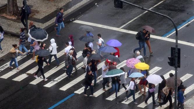 Com guarda-chuvas, pedestres atravessam rua do Centro do Rio Foto: Fabiano Rocha / Agência O Globo