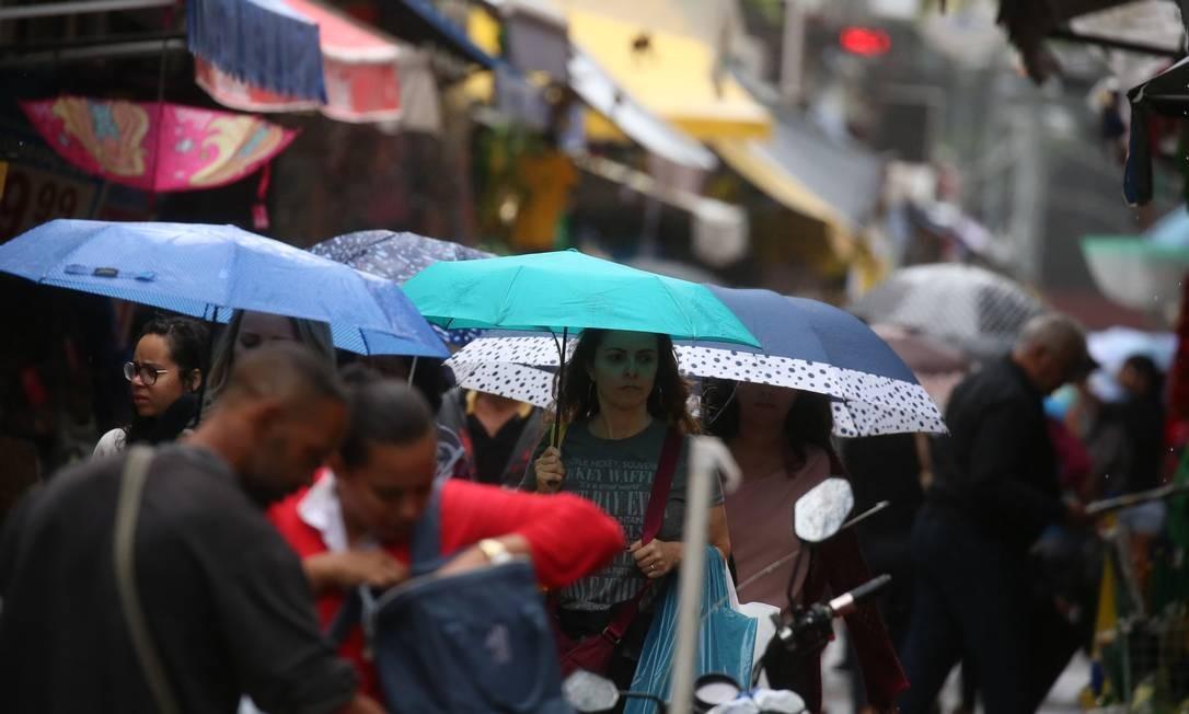 O Rio de Janeiro amanheceu chuvoso e com uma queda na temperatura, levando as pessoas a se protegerem da chuva Fabiano Rocha / Agência O Globo